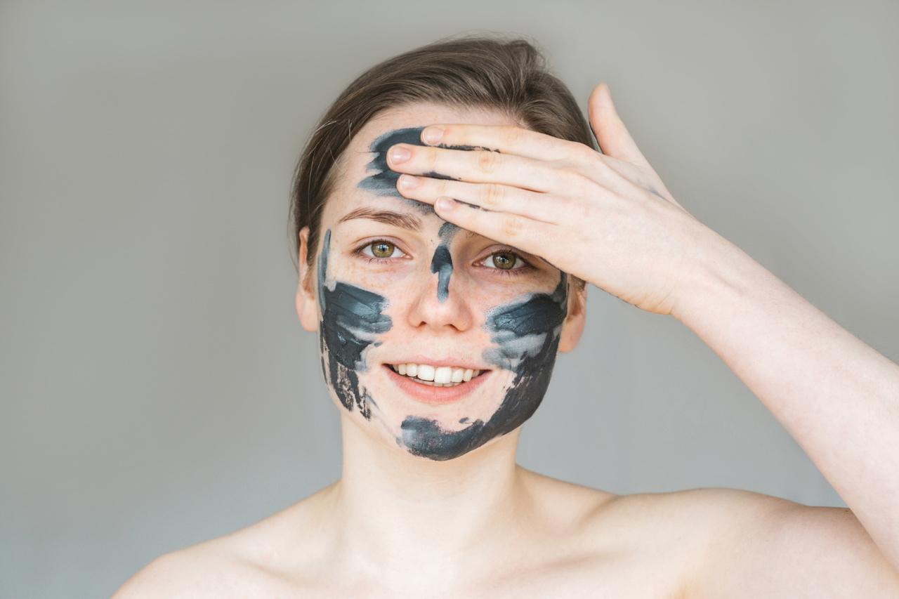 yüzüne kil maskesi süren genç ve güzel bir kadın