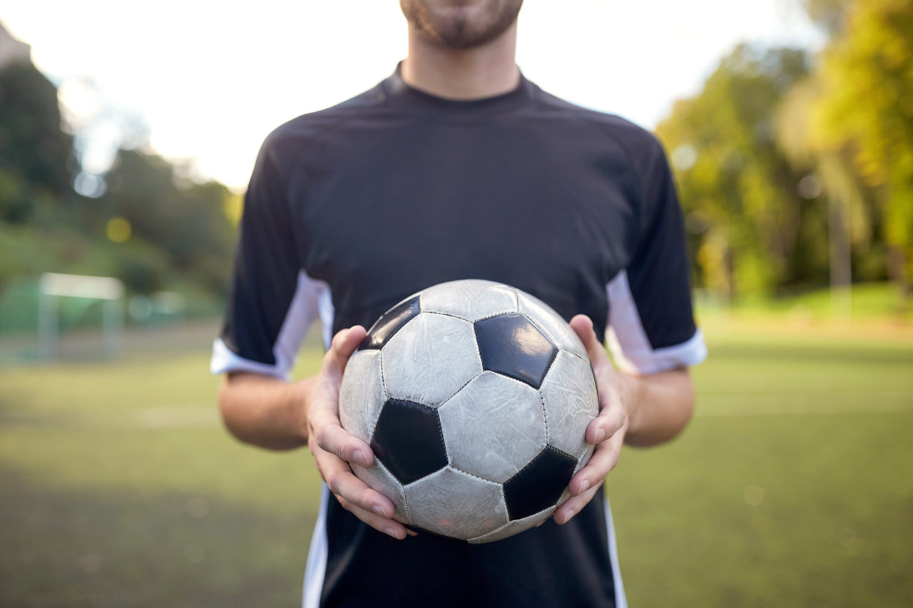 elinde futbol topu tutan genç ve yetenekli sporcu