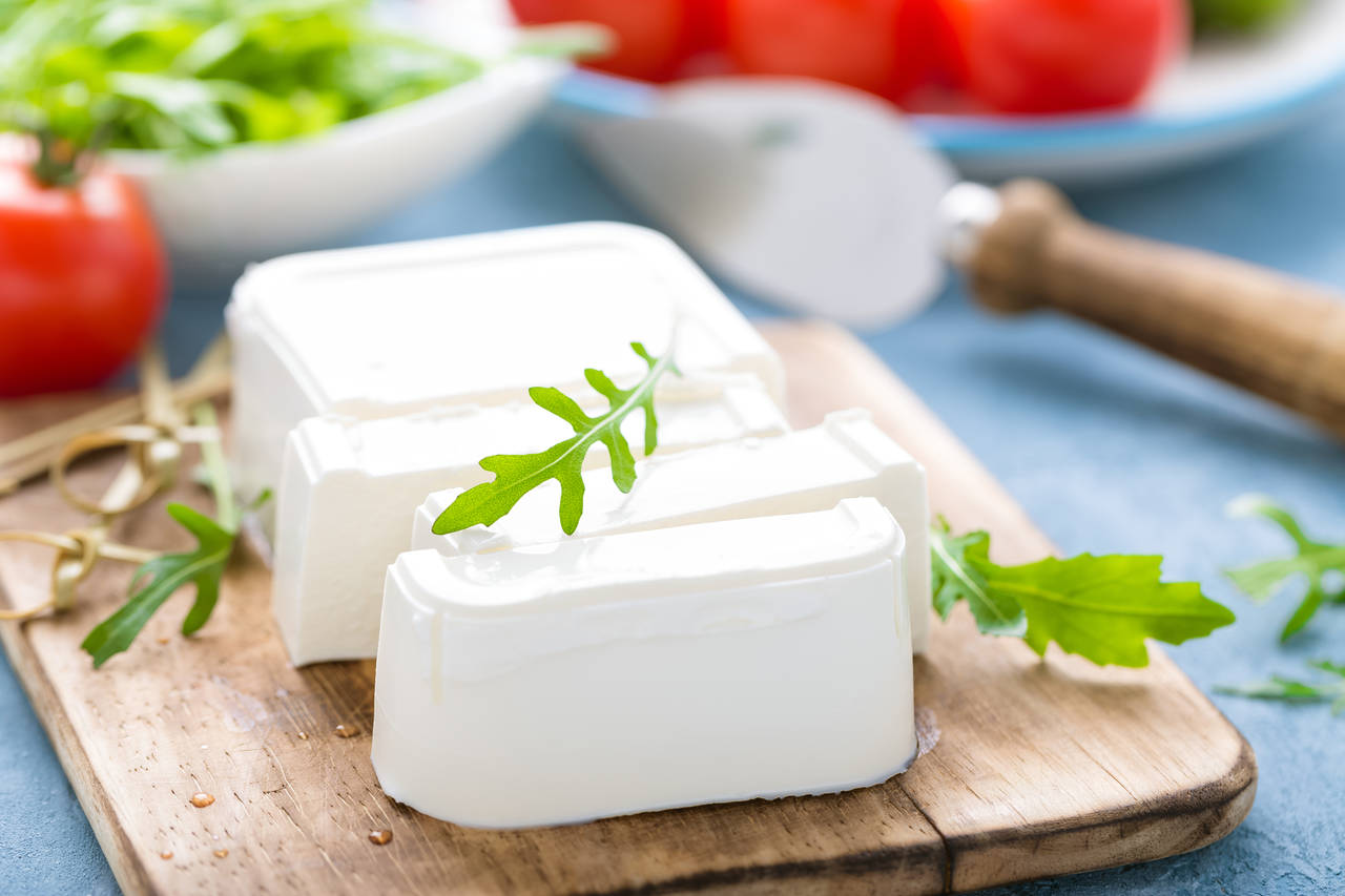 tabağın üzerinde duran dilimlenmiş beyaz peynir