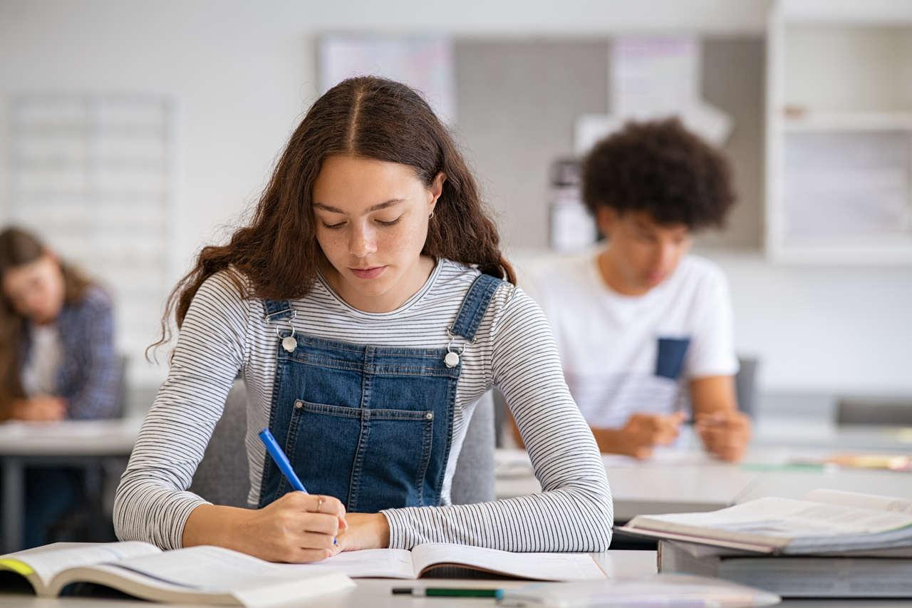 okulda defterine yazı yazan kız