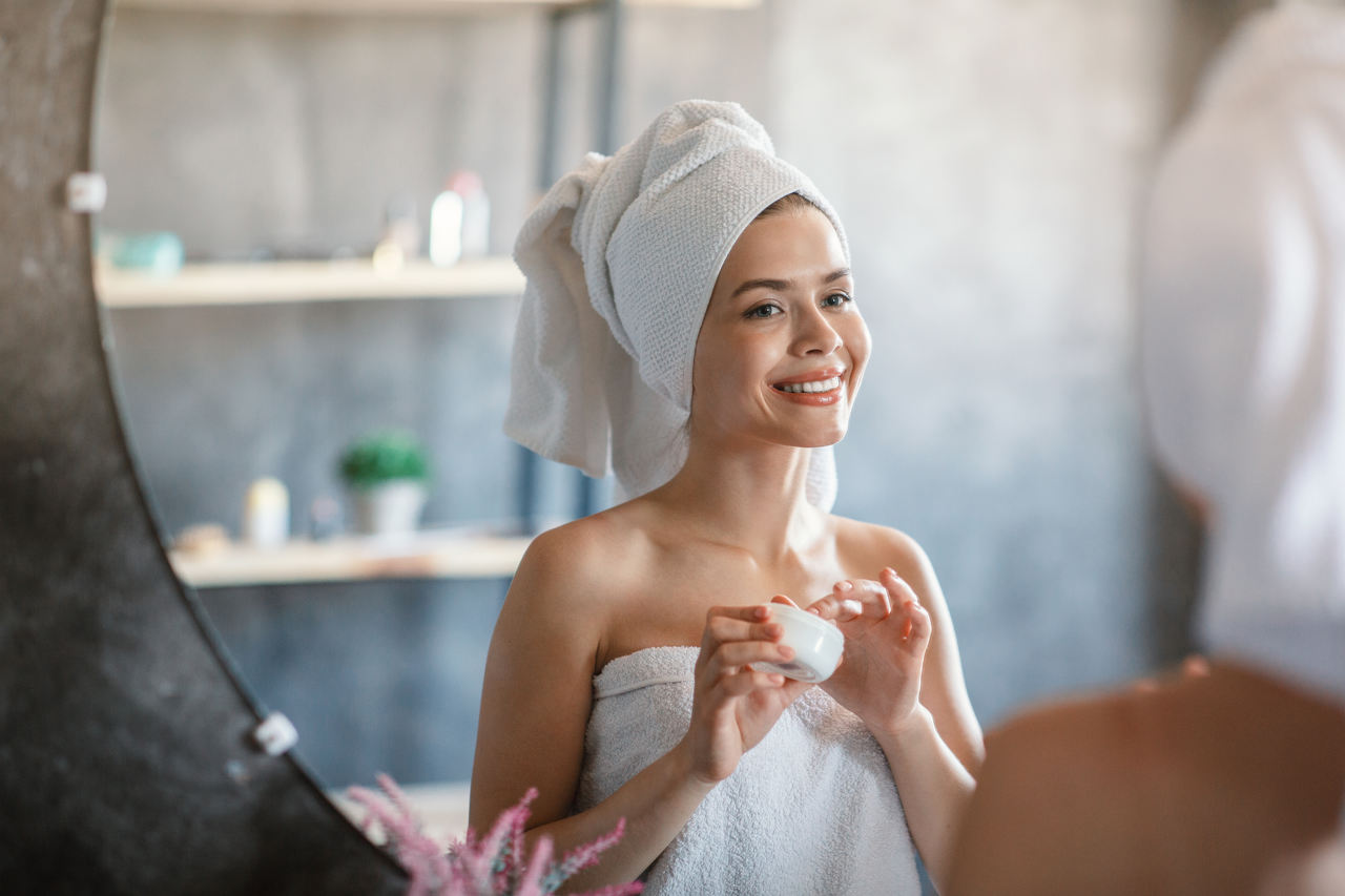 banyodan sonra cildine bakım yapan genç ve güzel bir kadın