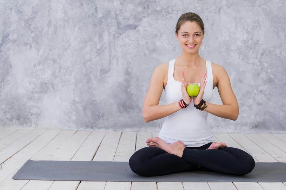 yoga yapan ve elinde elma tutan kadın