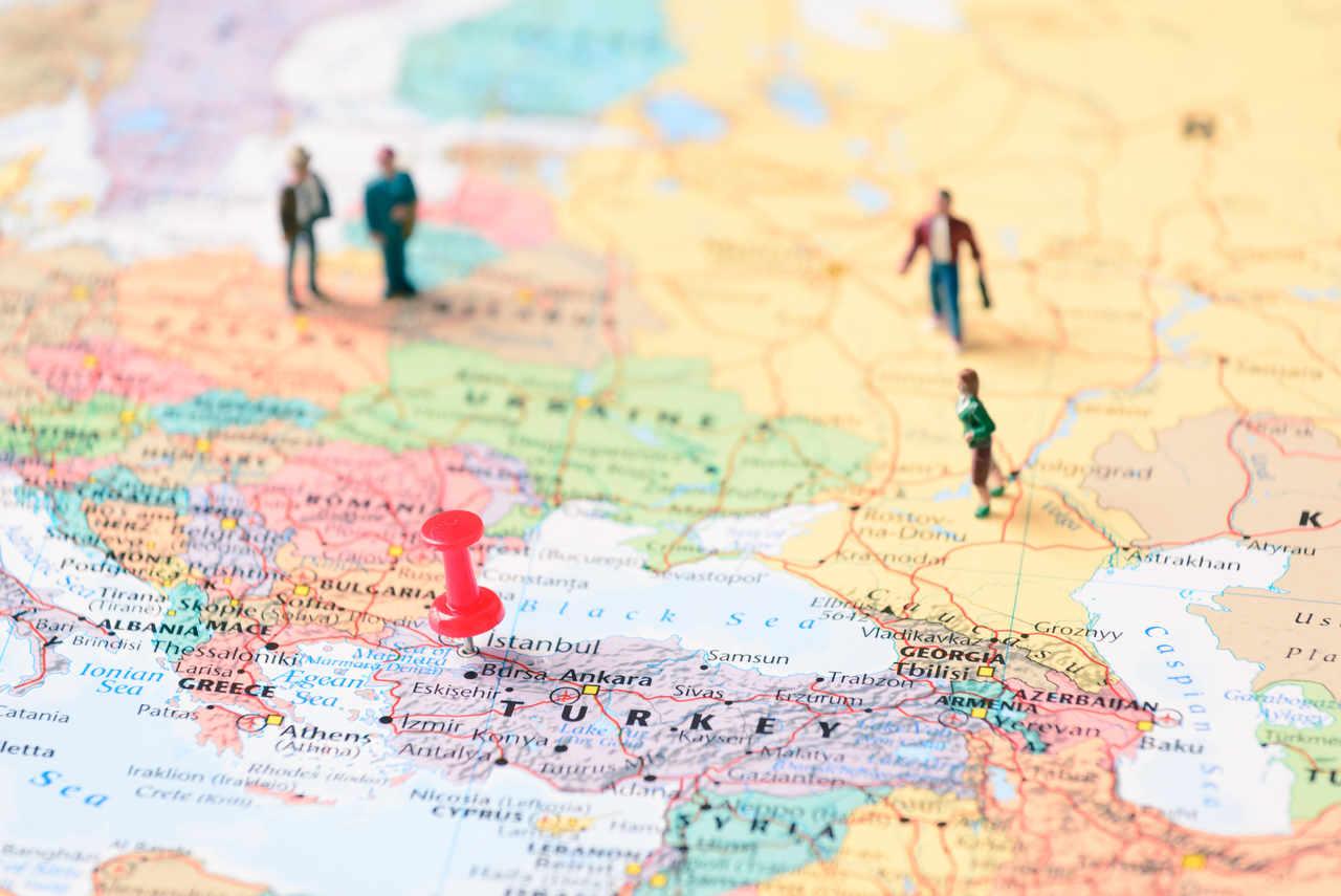 Bir dünya haritasının üzerinde işaretlenen Türkiye konumu ve o noktaya doğru yürüyen oyuncak insanlar