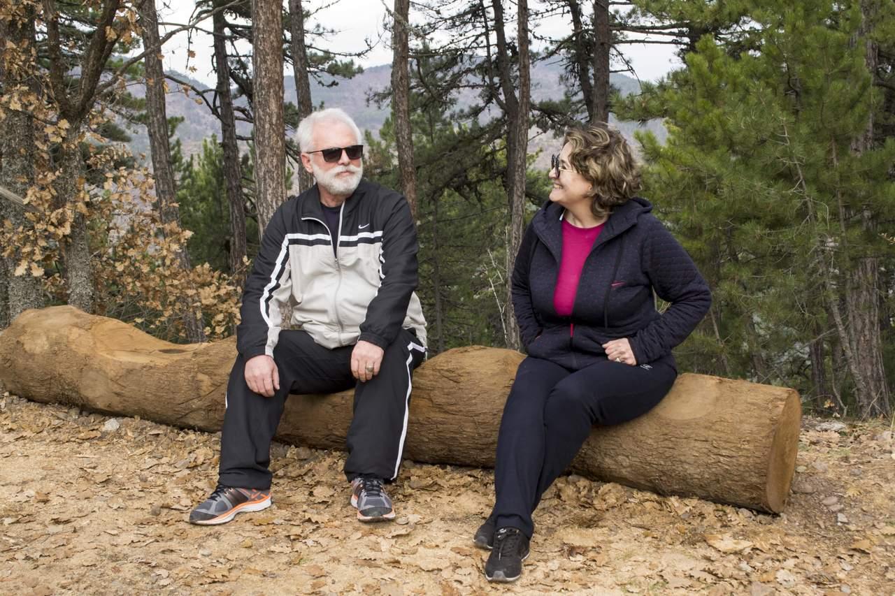 Bir ağaç kütüğü üzerinde oturan yaşlı kadın ile adam