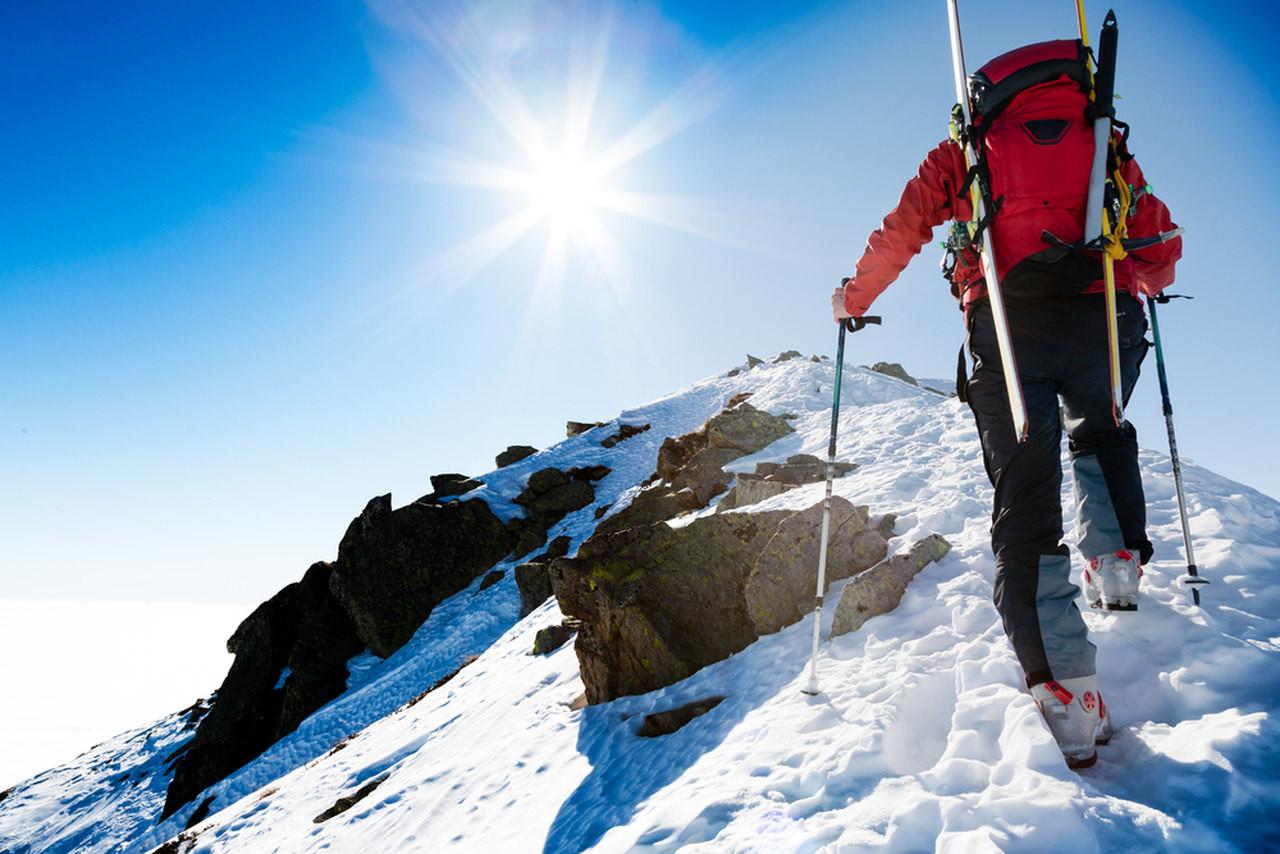 tırmanma ekipmanları ile kışın dağ zirvesine tırmanan sporcu