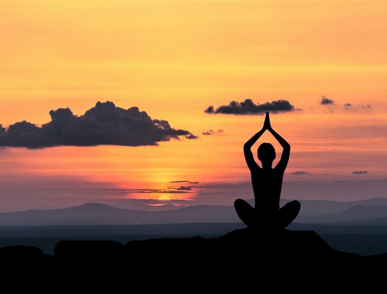 güneş batımında manzaraya karşı rahatlama egzersizi yapan bayan