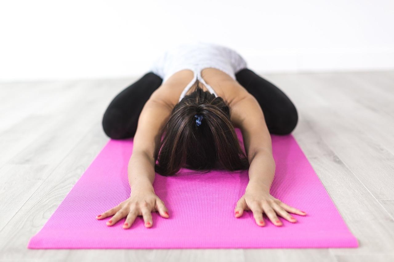 pembe yoga mat'i üzerinde yoga yapan bayan