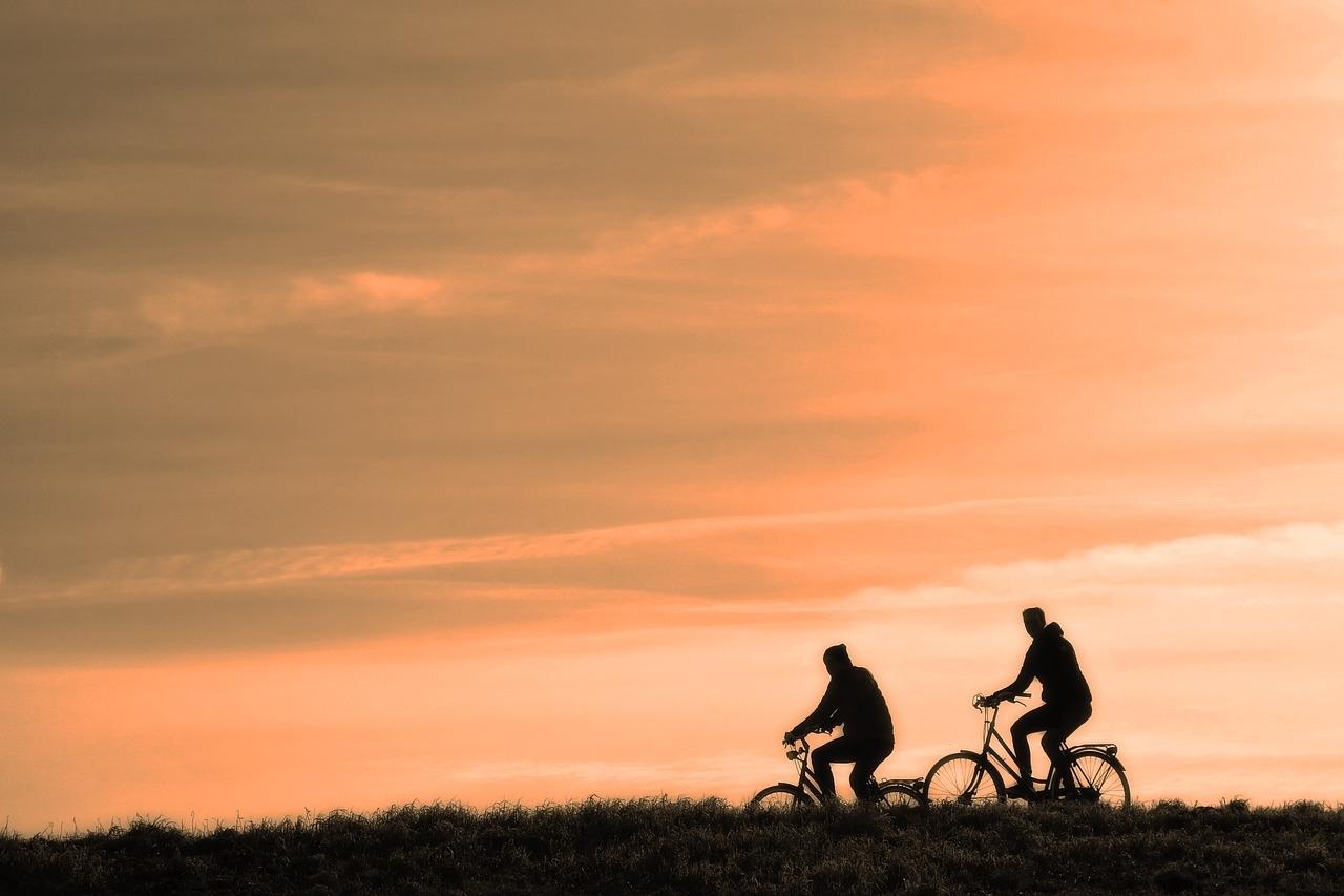 gün batımında manzara karşısında bisiklete binen iki kişi