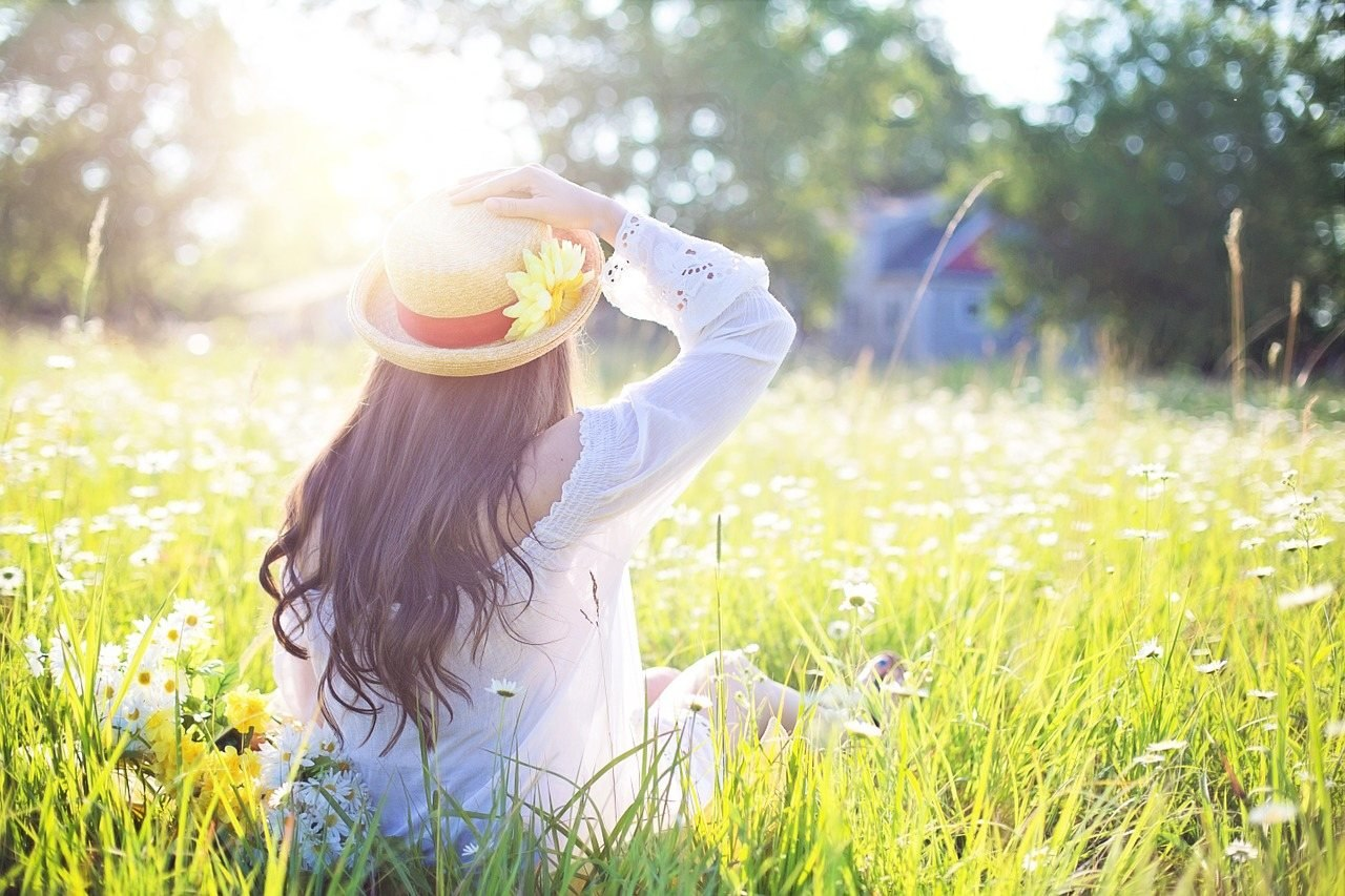çimlerin arasında güneşe doğru poz veren bayan
