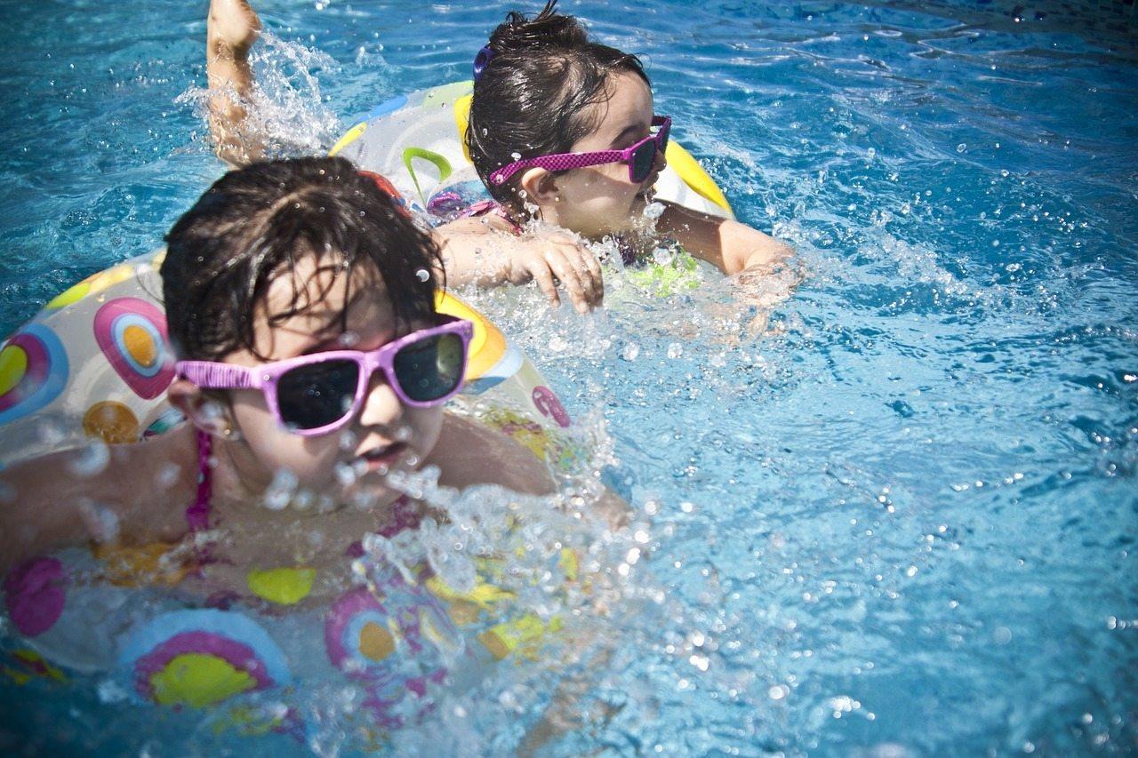 havuzda eğlenen iki kız çocuğu