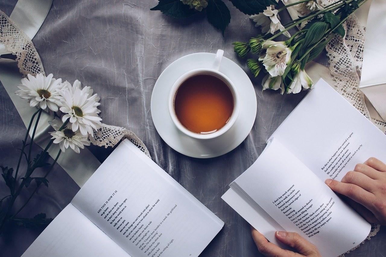 kahve fincanı eşliğinde kitap okuyan kişi